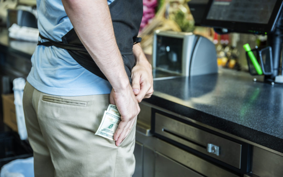 A male employee stealing cash at the checkout in a store